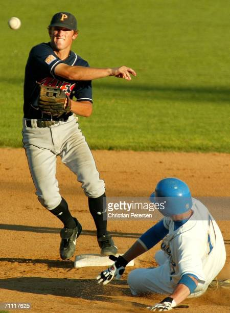 Danny Worth of the Pepperdine Waves throws to first base over Josh Roenicke of the UCLA Bruins to complete a double play during the NCAA college...