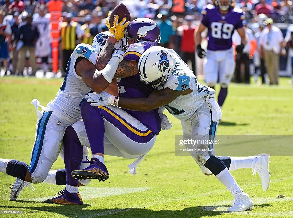 Da'Norris Searcy #21 and Wesley Woodyard #59 of the Tennessee Titans sandwich tackle Kyle Rudolph #82 of the Minnesota Vikings, knocking the ball loose during the second half at Nissan Stadium on September 11, 2016 in Nashville, Tennessee.
