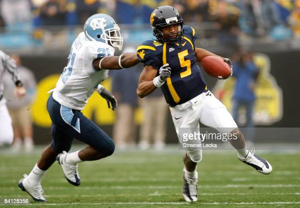 Da'Norris Searcy of the North Carolina Tar Heels grabs Pat White of the West Virginia Mountaineers during the Meineke Car Care Bowl on December 27...