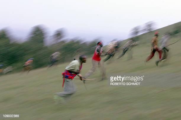 Dans les collines du Trans Mara, combats d'archers pour une élection avortée by Francois AusseillKalenjin warriors rush up a battle field hill as...