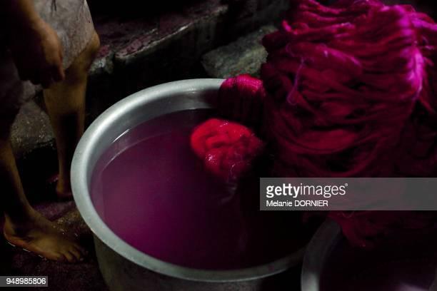 Dans les petites rues de Bangalore les teintureries teintent la soie brute pour quelques roupies Une poudre chimique est melangee a de l'eau chaude...