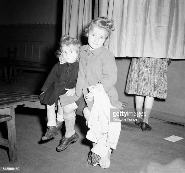 Dans un bureau de vote un bébé et son petit frère attendent devant l'isoloir où se trouve leur maman qui vote à Paris France en 1946