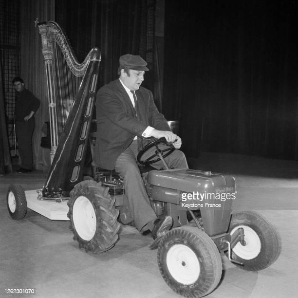 Dans un de ses sketchs, Raymond Devos jouant de la harpe tirée par un tracteur, en France le 22 septembre 1964.