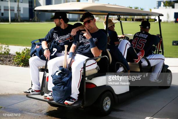 Dansby Swanson and Austin Riley of the Atlanta Braves take a golf cart to take batting practice during a team workout at CoolToday Park on February...