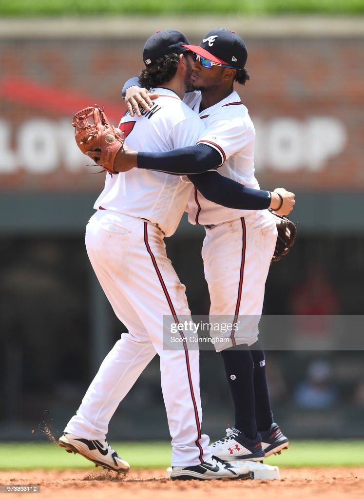Dansby Swanson #7 and Ozzie Albies #1 of the Atlanta Braves celebrate after the game against the New York Mets at SunTrust Field on June 13, 2018 in Atlanta, Georgia.