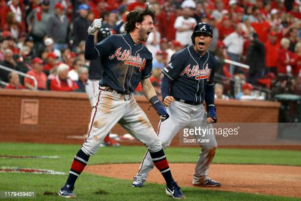 Dansby Swanson and Rafael Ortega of the Atlanta Braves celebrate after scoring the go-ahead runs against the St. Louis Cardinals during the ninth...
