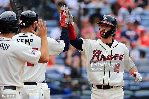 Dansby Swanson celebrates scoring with Matt Kemp of the Atlanta Braves in the fourth inning against the Washington Nationals at Turner Field on...