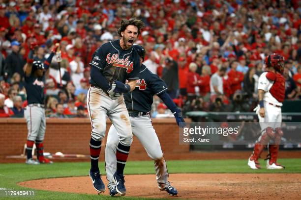 Dansby Swanson of the Atlanta Braves celebrates after scoring a run against the St. Louis Cardinals during the ninth inning in game three of the...
