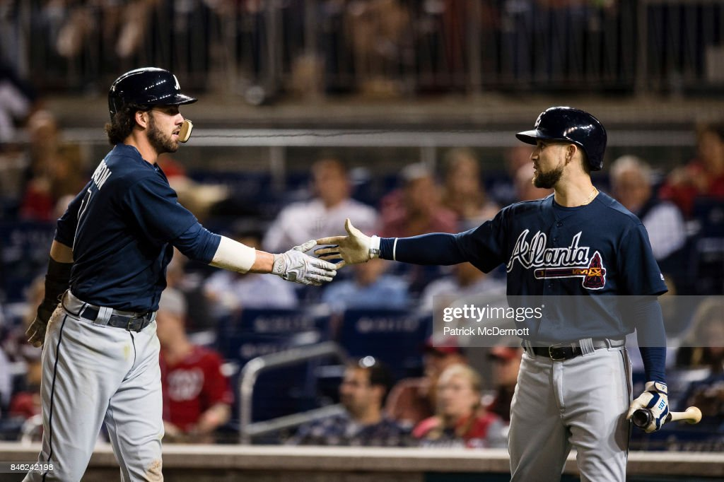 Dansby Swanson #7 of the Atlanta Braves celebrates with Ender Inciarte #11 after scoring on a single hit by starting pitcher Julio Teheran #49 (not pictured) in the sixth inning against the Washington Nationals at Nationals Park on September 12, 2017 in Washington, DC.