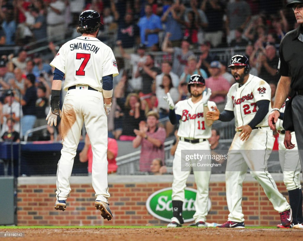 Dansby Swanson #7 of the Atlanta Braves celebrates with Matt Kemp #27 and Ender Inciarte #11 after scoring a sixth inning run against the Arizona Diamondbacks at SunTrust Park on July 15, 2017 in Atlanta, Georgia.