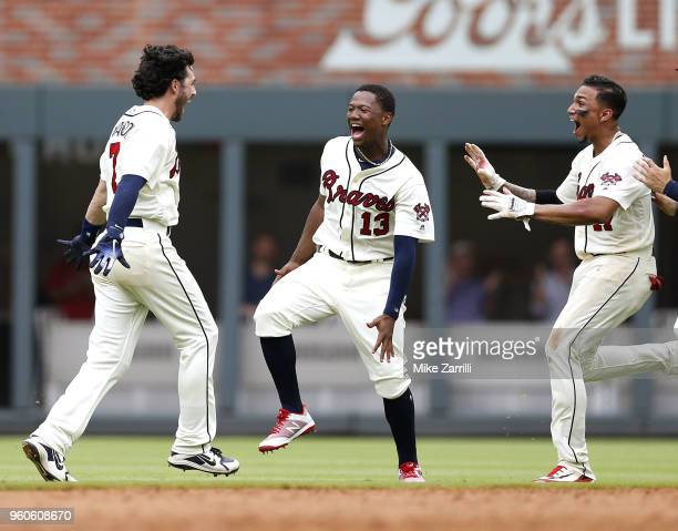 Dansby Swanson of the Atlanta Braves celebrates with Ronald Acuna Jr #13 and Johan Camargo after Swanson hit a tworun gamewinning walkoff single in...