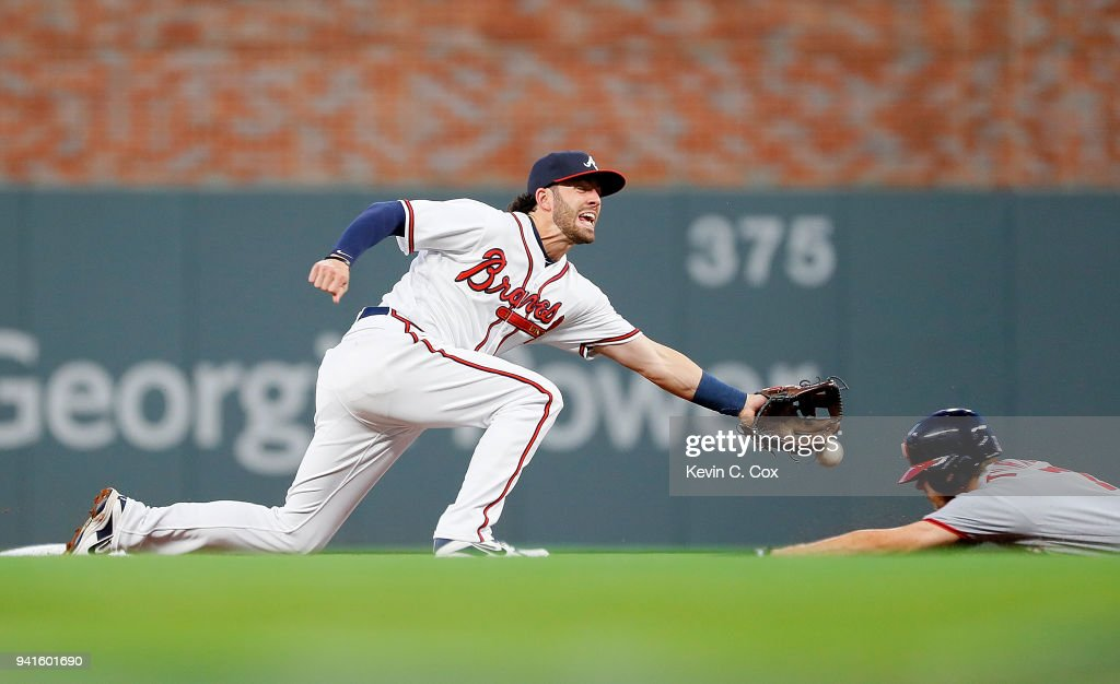 Dansby Swanson #7 of the Atlanta Braves fails to pull in this throw as Trea Turner #7 of the Washington Nationals steals second base in the first inning at SunTrust Park on April 3, 2018 in Atlanta, Georgia.