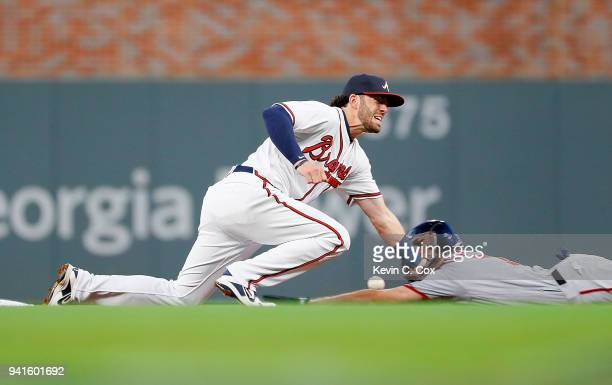 Dansby Swanson of the Atlanta Braves fails to pull in this throw as Trea Turner of the Washington Nationals steals second base in the first inning at...