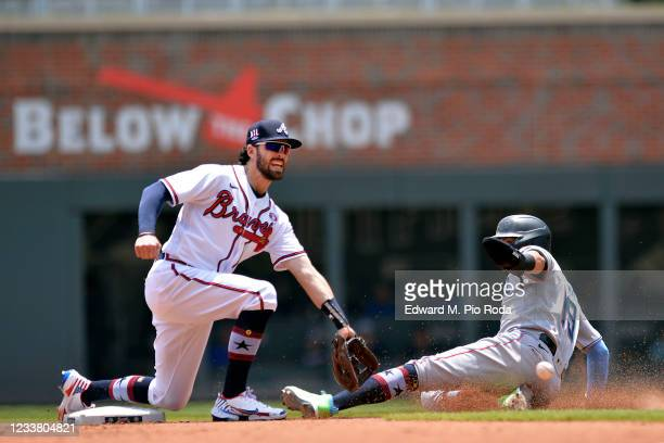 Dansby Swanson of the Atlanta Braves fields a late throw as Miguel Rojas of the Miami Marlins steals second base in the fourth inning at Truist Park...