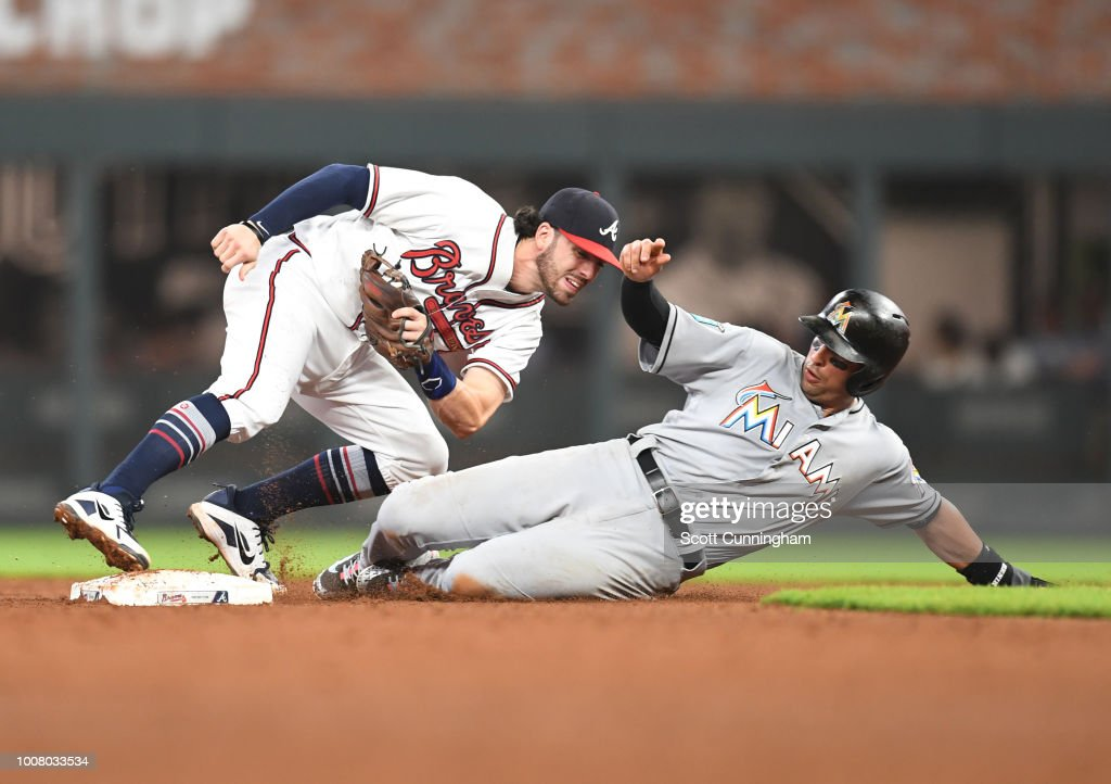 Dansby Swanson #7 of the Atlanta Braves forces out Martin Prado #14 of the Miami Marlins at second base during the eighth inning at SunTrust Park on July 30, 2018 in Atlanta, Georgia.