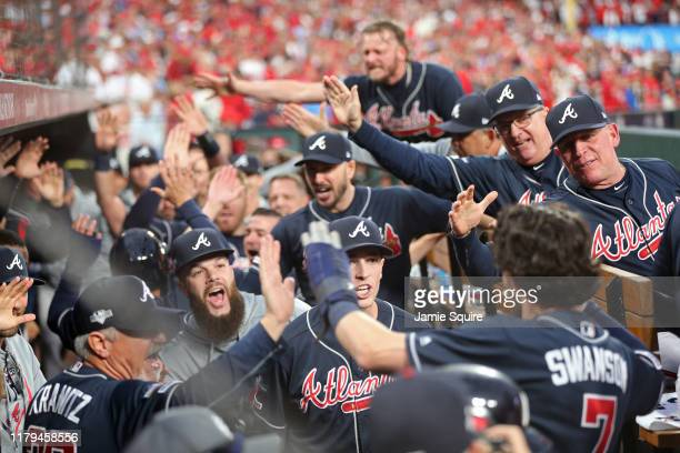 Dansby Swanson of the Atlanta Braves is congratulated by his teammates in the dugout after hitting an RBI double and scoring a run during the ninth...