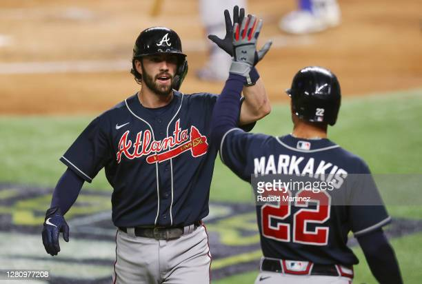 Dansby Swanson of the Atlanta Braves is congratulated by Nick Markakis after hitting a solo home run against the Los Angeles Dodgers during the...