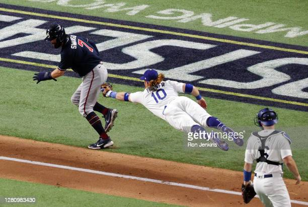 Dansby Swanson of the Atlanta Braves is tagged out by Justin Turner of the Los Angeles Dodgers in a rundown between third base and home plate during...