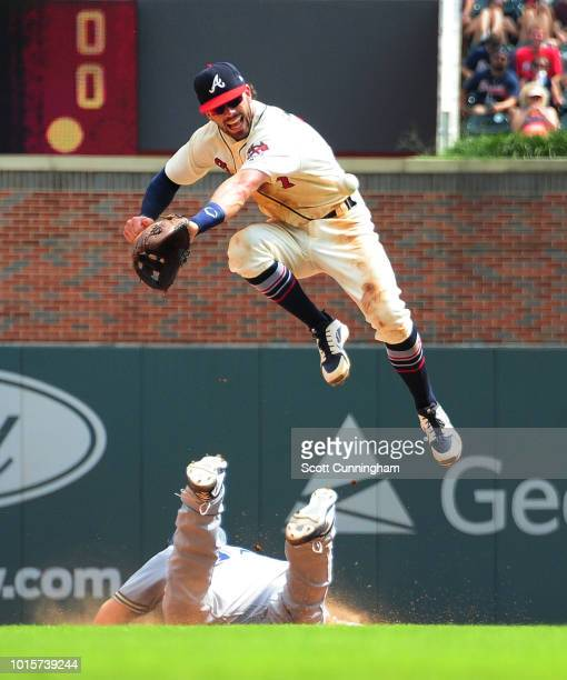 Dansby Swanson of the Atlanta Braves is unable to make the catch of an errant pickoff attempt as Erik Kratz of the Milwaukee Brewers dives back...
