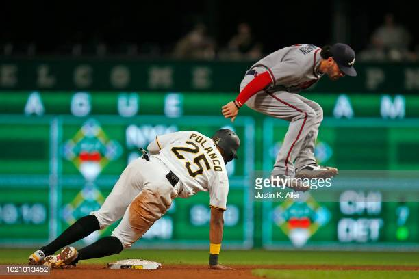 Dansby Swanson of the Atlanta Braves jumps over Gregory Polanco of the Pittsburgh Pirates in the seventh inning at PNC Park on August 21 2018 in...