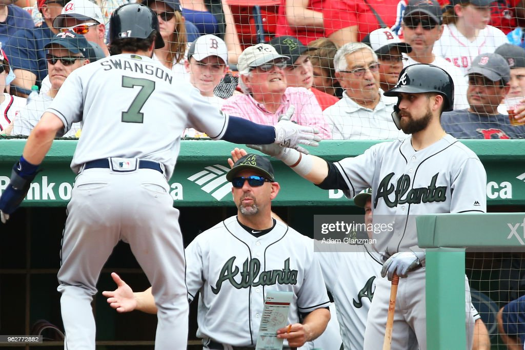 Dansby Swanson #7 of the Atlanta Braves returns to the dugout after scoring in the fourth inning of a game against the Boston Red Sox at Fenway Park on May 26, 2018 in Boston, Massachusetts.