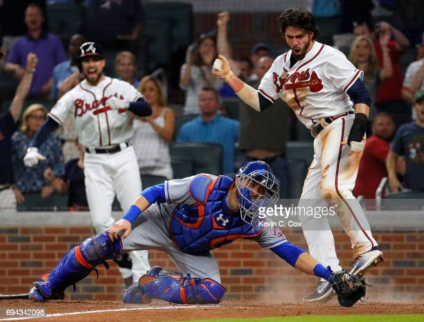 Dansby Swanson of the Atlanta Braves scores the game-winning run as he slides past Travis d'Arnaud of the New York Mets on a RBI hit by Rio Ruiz in...