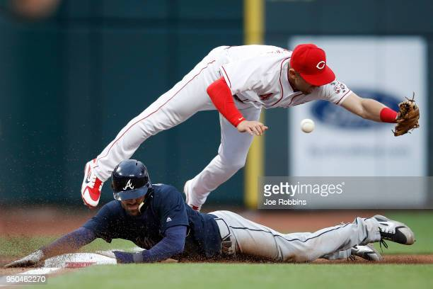 Dansby Swanson of the Atlanta Braves slides at third base ahead of the throw to Cliff Pennington of the Cincinnati Reds in the third inning of a game...
