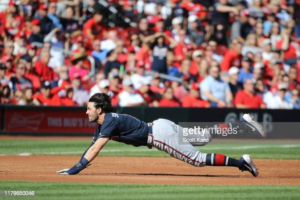 Dansby Swanson of the Atlanta Braves slides in safely to third base against the St Louis Cardinals during the third inning in game four of the...