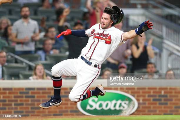 Dansby Swanson of the Atlanta Braves slides into home plate on a single from Ronald Acuna Jr #13 of the Atlanta Braves in the eighth inning during...