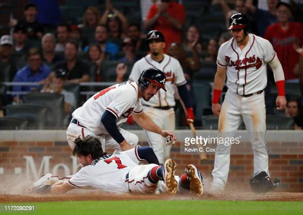 Dansby Swanson of the Atlanta Braves slides safely across home plate into Matt Joyce as they and Josh Donaldson score on a threeRBI double by Tyler...