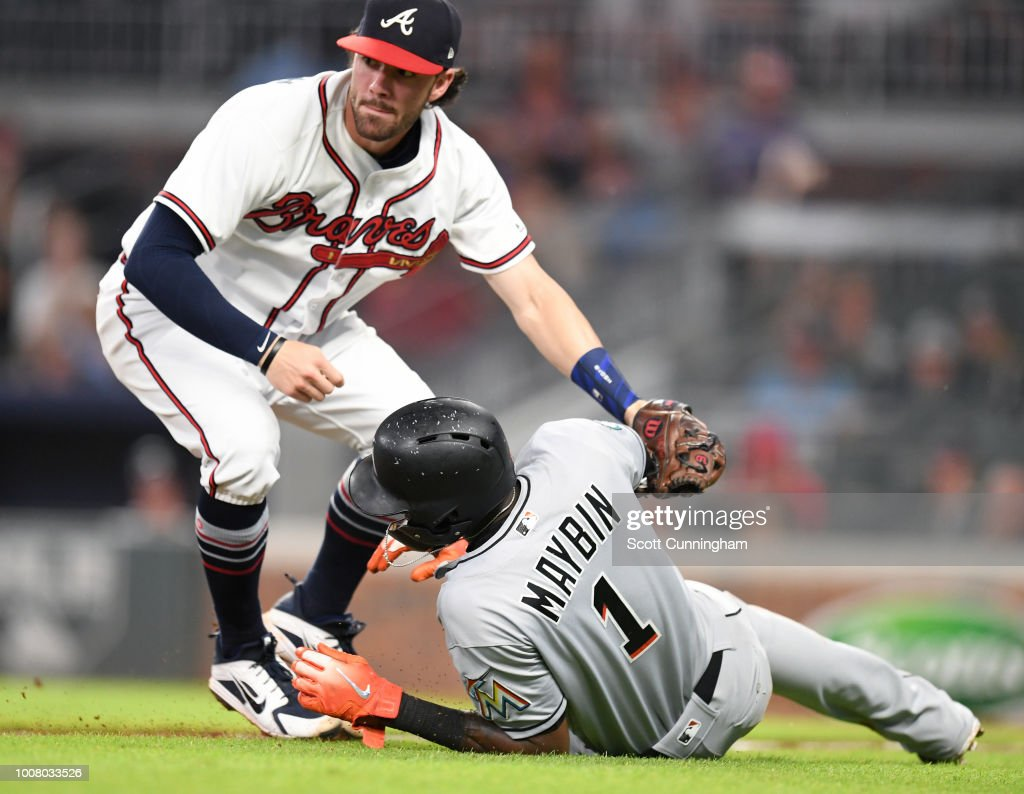 Dansby Swanson #7 of the Atlanta Braves tags out Cameron Maybin #1 of the Miami Marlins after a seventh inning run-down at SunTrust Park on July 30, 2018 in Atlanta, Georgia.