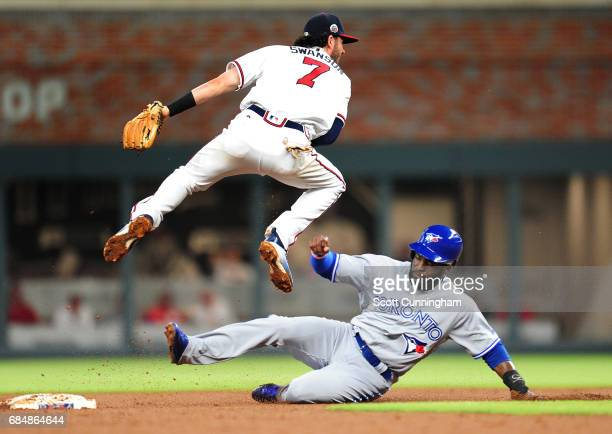 Dansby Swanson of the Atlanta Braves turns a fourth inning double play against Dwight Smith Jr #15 of the Toronto Blue Jays at SunTrust Park on May...