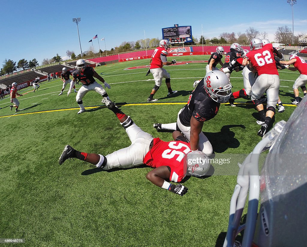 Dante Allen #73 of the Stony Brook Defense rushes past Armani Garrick #55 of the Stony Brook Offense who is protecting Quarterback Conor Bednarski during their Spring Football Game at Kenneth P. LaValle Stadium on April 26, 2014 in Stony Brook, New York.