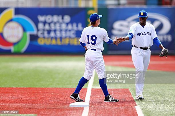 Dante Bichette Jr #19 highfives Thyago Vieira of Team Brazil during workouts at MCU Park prior to the start of the 2016 World Baseball Classic...