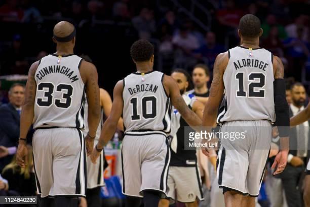 Dante Cunningham DeMar DeRozan and LaMarcus Aldridge of the San Antonio Spurs walk to the bench against the Philadelphia 76ers at the Wells Fargo...