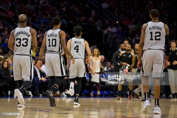 Dante Cunningham DeMar DeRozan Derrick White and LaMarcus Aldridge of the San Antonio Spurs walk to the bench against the Philadelphia 76ers at the...
