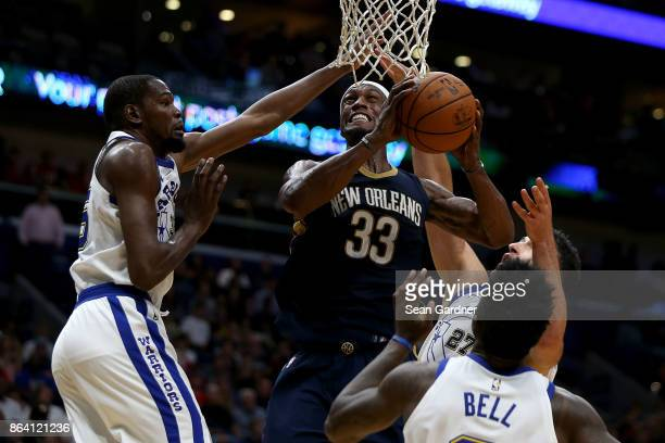 Dante Cunningham of the New Orleans Pelicans shoots over Kevin Durant of the Golden State Warriors and Zaza Pachulia of the Golden State Warriors...