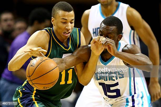 Dante Exum of the Utah Jazz and Kemba Walker of the Charlotte Hornets go after a loose ball during their game at Time Warner Cable Arena on December...