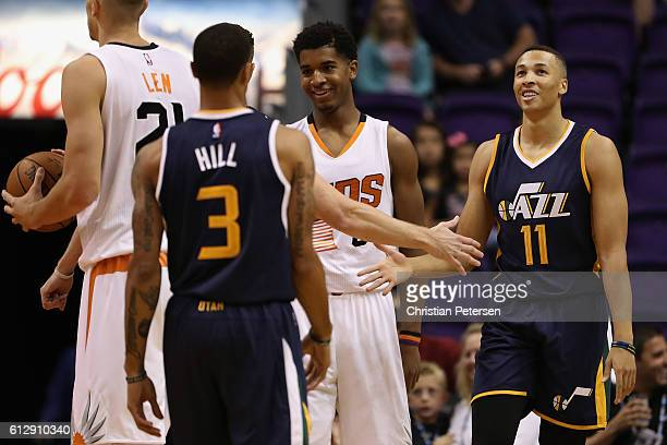 Dante Exum of the Utah Jazz high fives George Hill after scoring against the Phoenix Suns during the first half of the preseason NBA game at Talking...