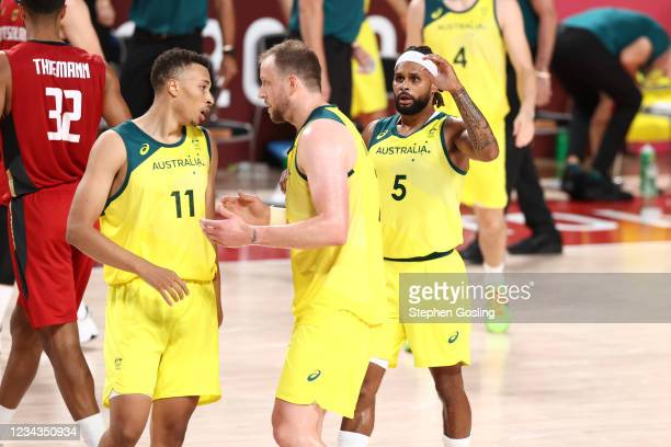 Dante Exum talks with Patty Mills and Joe Ingles of the Australia Men's National Team during the game against the Germany Men's National Team during...