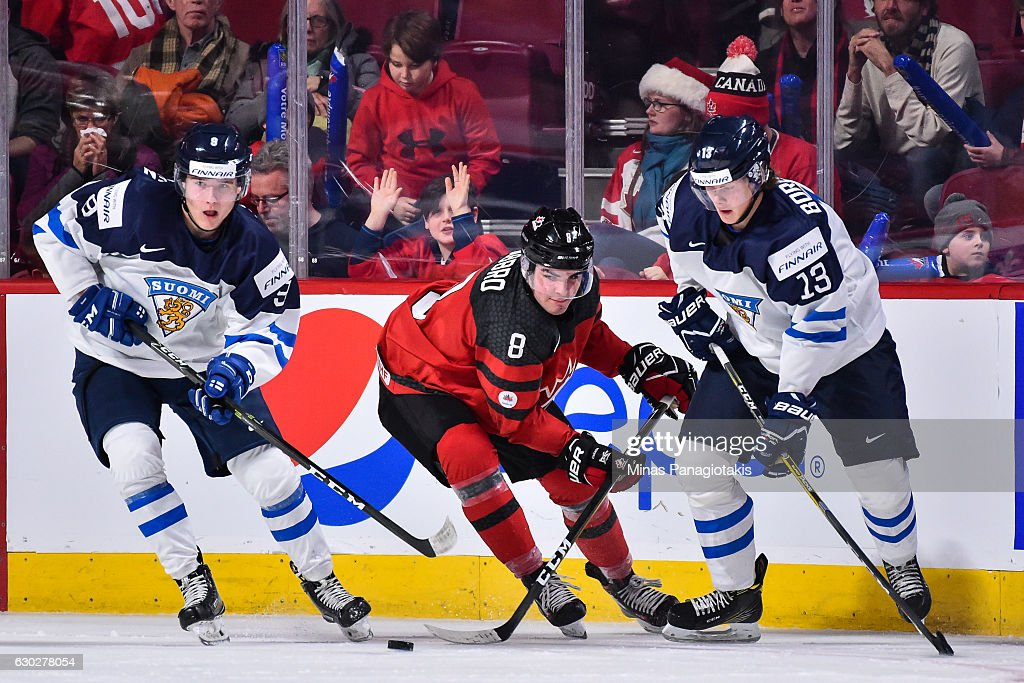 Dante Fabbro #8 of Team Canada tries to skate the puck in-between Janne Kuokkanen #9 and Henrik Borgstrom of Team Finland #13 during the IIHF exhibition game at the Bell Centre on December 19, 2016 in Montreal, Quebec, Canada. Team Canada defeated Team Finland 5-0.