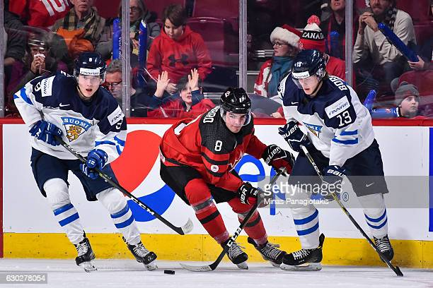 Dante Fabbro of Team Canada tries to skate the puck inbetween Janne Kuokkanen and Henrik Borgstrom of Team Finland during the IIHF exhibition game at...