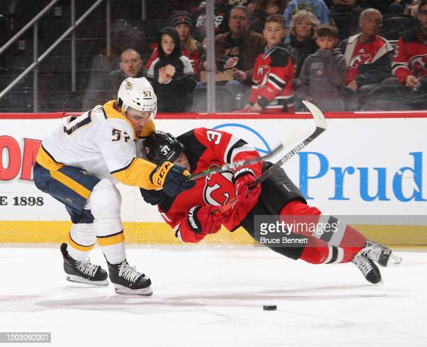 Dante Fabbro of the Nashville Predators holds on to Pavel Zacha of the New Jersey Devils during the first period at the Prudential Center on January...