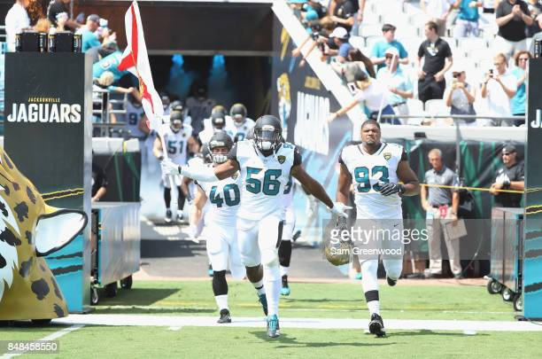 Dante Fowler of the Jacksonville Jaguars takes the field with his teammates and a Florida state flag prior to the start of a game against the...