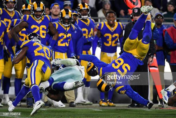 Dante Fowler of the Los Angeles Rams is upended while trying to tackle Ezekiel Elliott of the Dallas Cowboys in the third quarter in the NFC...