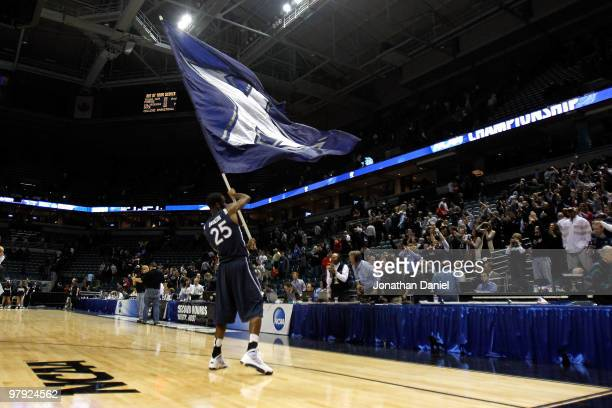 Dante Jackson of the Xavier Musketeers picks up the team flag and celebrates after defeating the Pittsburgh Panthers during the second round of the...
