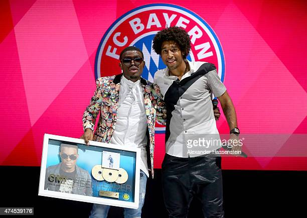 Dante of Bayern Muenchen hands over the 'Golden Record' award to singer Omi during the FC Bayern Muenchen Bundesliga Champions Dinner at Postpalast...