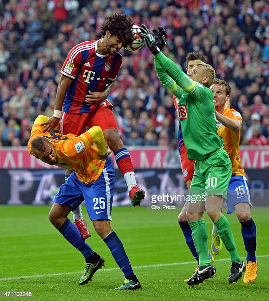 Dante of Bayern Muenchen heads the ball against John Anthony Brooks and Sascha Burchert during the game FC Bayern Muenchen against Hertha BSC on...