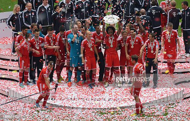 Dante of Bayern Muenchen lifts the Bundesliga trophy with his teammates following their match against Augsburg at the Allianz Arena on May 11 2013 in...
