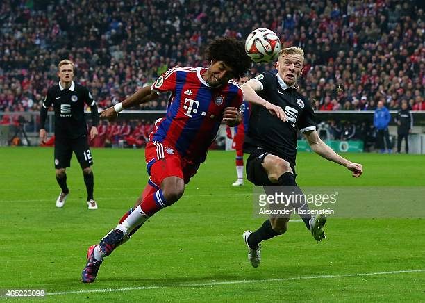 Dante of FC Bayern Muenchen heads the ball under the pressure of Maximilian Sauer of Eintracht Braunschweig during the round of 16 DFB Cup match...